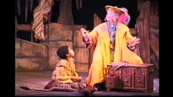 Stage scene featuring a maimed boy and a heavily-robed adult