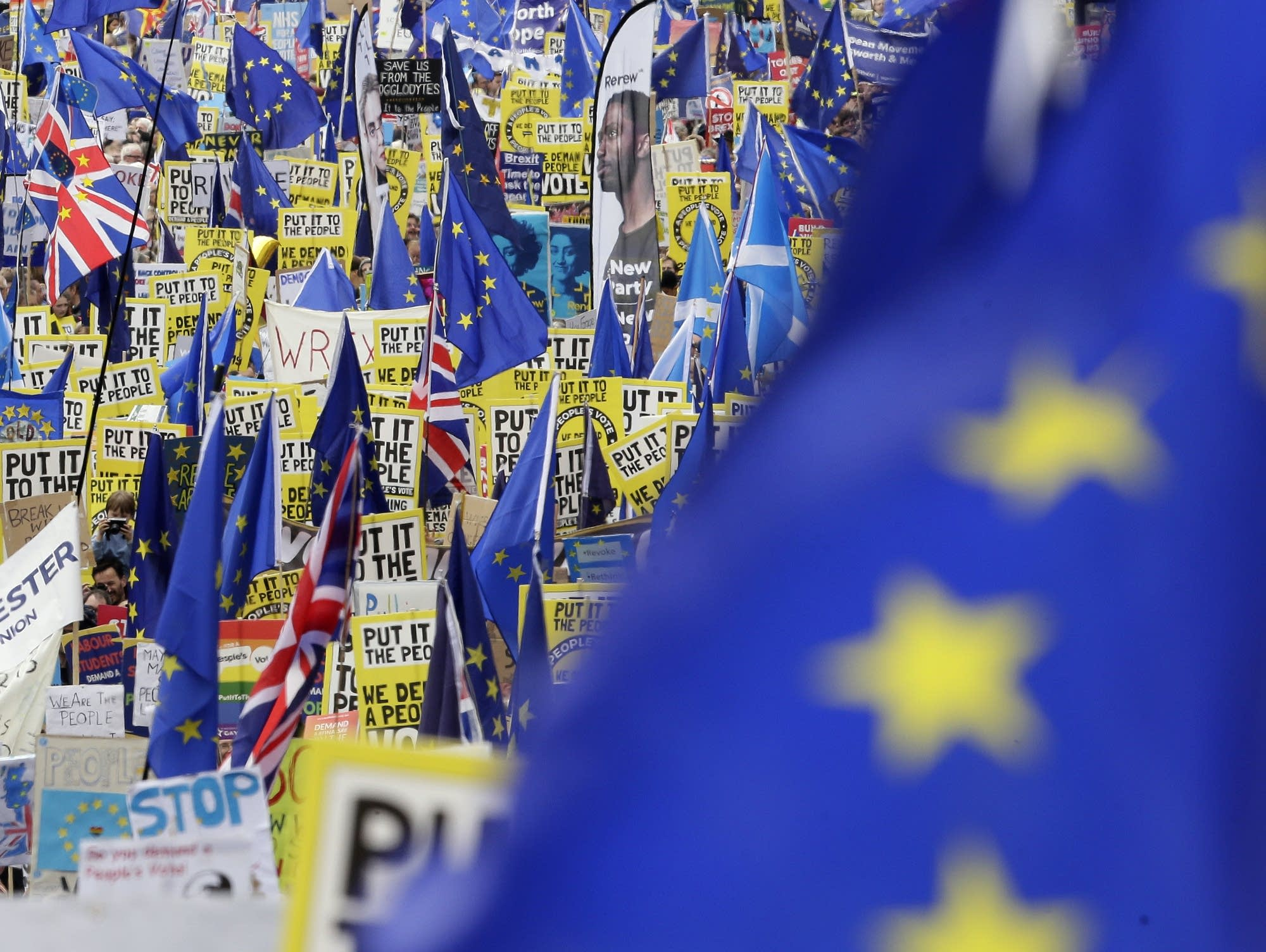 Demonstrators carry posters and flags during an anti-Brexit march