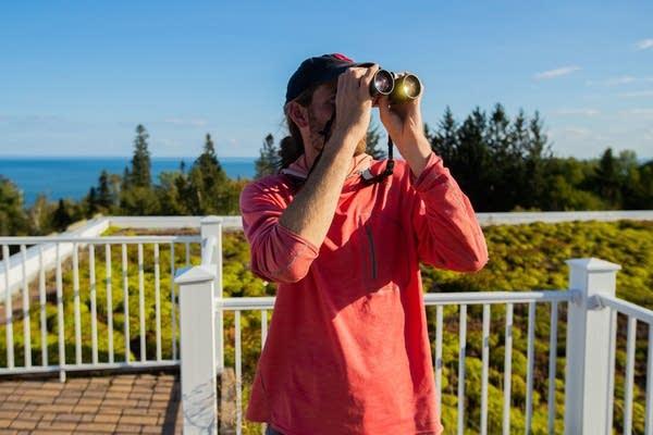 A bird-watcher scans the skies.