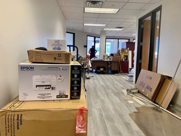 Boxes and construction equipment sit in a hallway of an office.