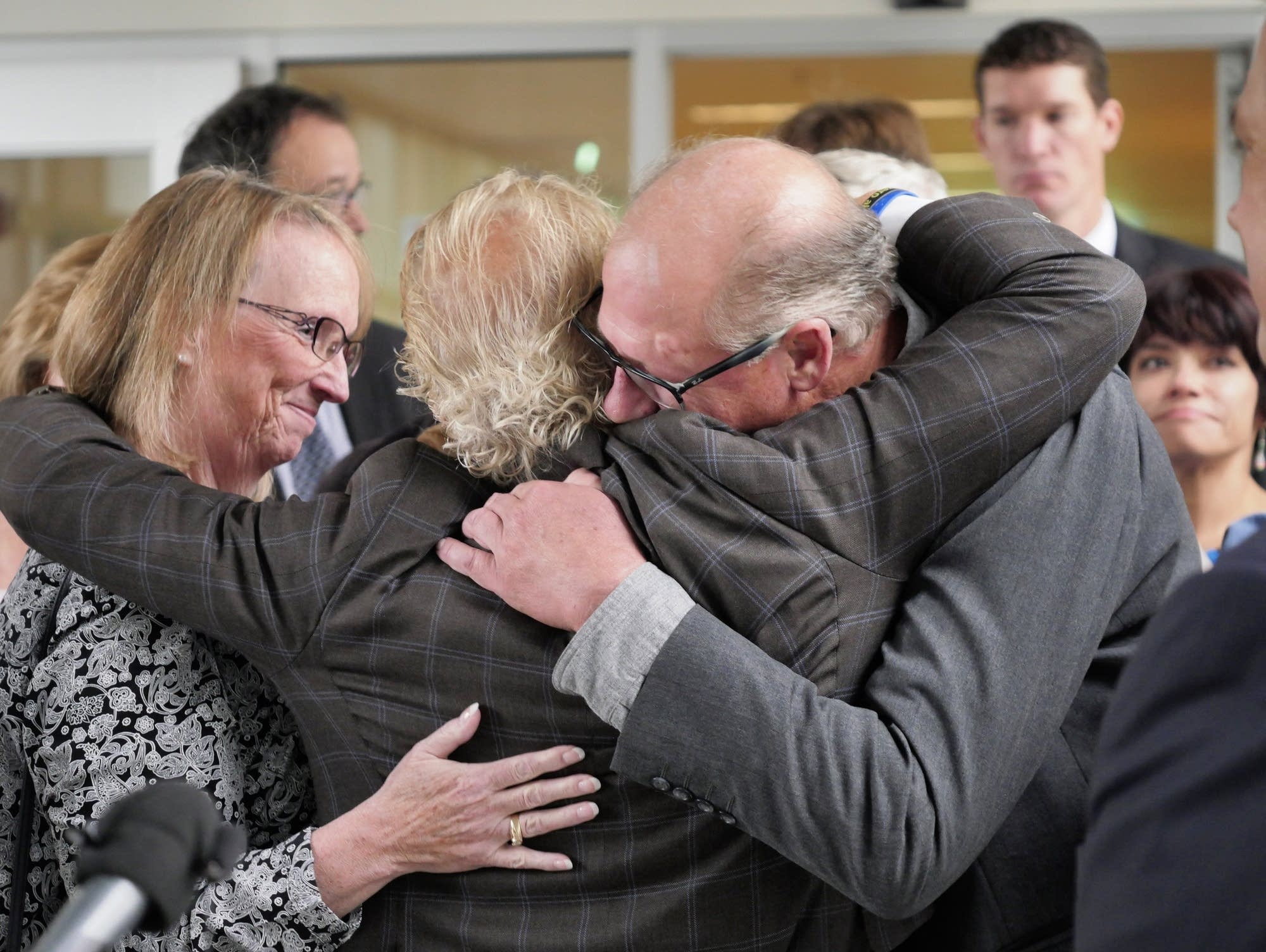 Victims' attorney Jeff Anderson, center, embraces his clients