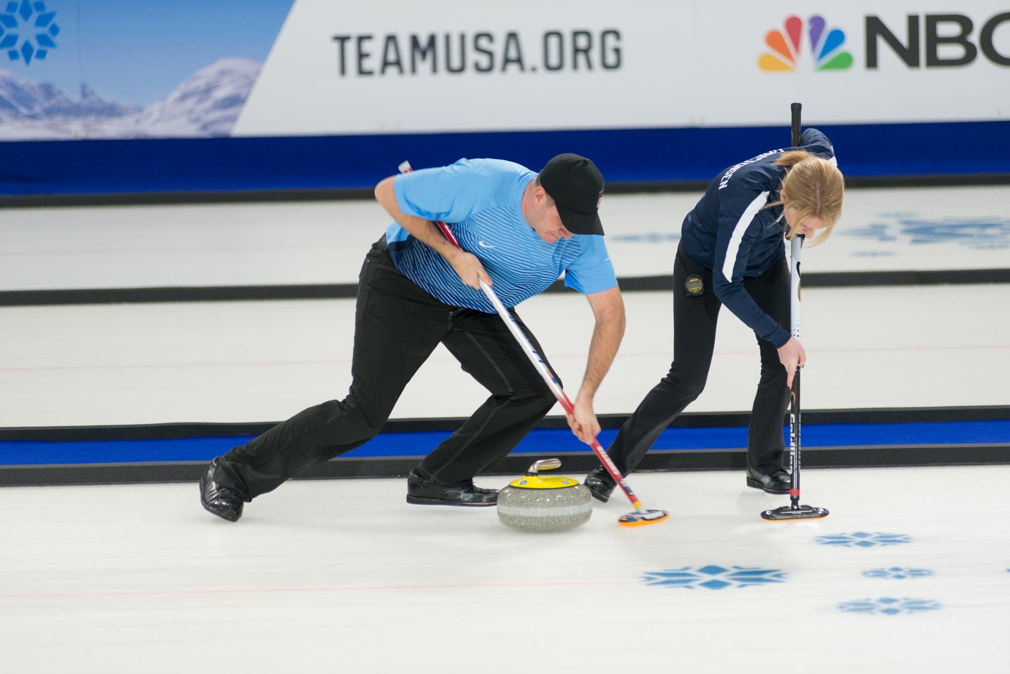 John Shuster and Cory Christensen sweep hard in front of their stone.