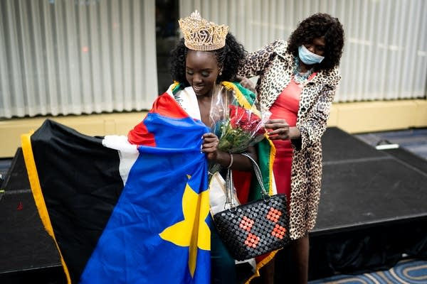 A woman in a crown is draped in a flag.