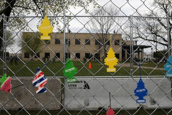 Air fresheners hang from a fence.
