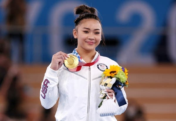 A woman stands with her Olympic gold medal.