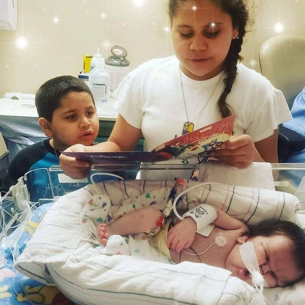 Phoenix Gilmore and Montaque read a story to their baby brother Zephyr.