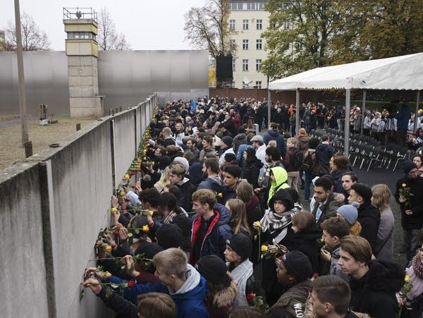 Young people stick flowers in remnants of the Berlin Wall