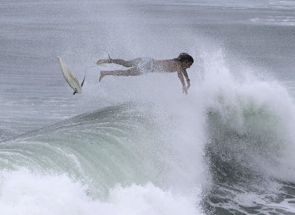 A surfer crashes into the water as a subtropical approaches on Monday.