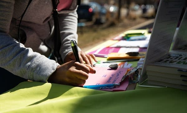 a person signs a paper with a pen