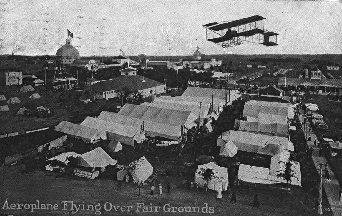 A 1912 postcard featuring a plane over the Minnesota State Fairgrounds.