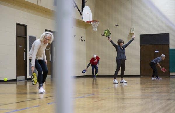 A person raises their arms in a gym.