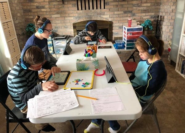Four teenagers use tablets to do work as they sit at a table.