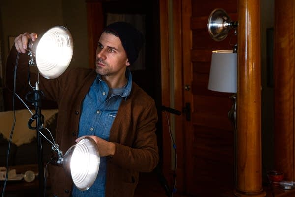 A man adjusts stage lights in an apartment.