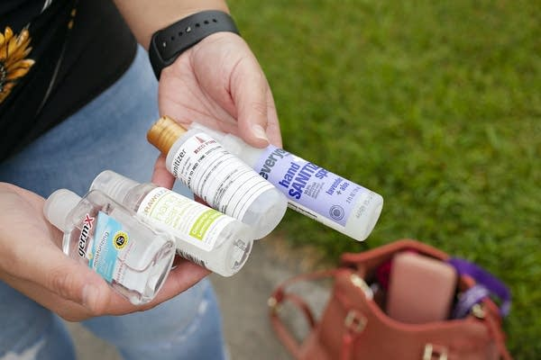 A person holding four bottles of hand sanitizer.