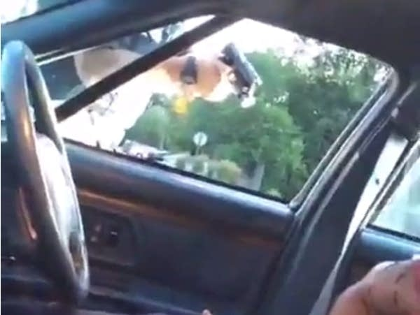 An officer points his gun into a vehicle.