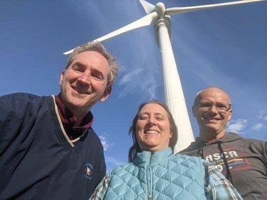 Paul Huttner, Amy Feek and Matt Podhradsky beneath a wind turbine in Chaska