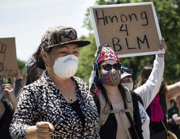 "One person in a crowd holding a sign that reads ""Hmong 4 BLM"""
