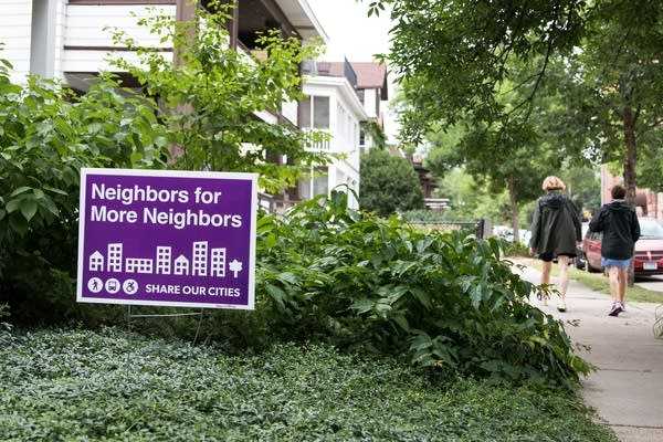 A Neighbors for More Neighbors sign sits in a front yard.