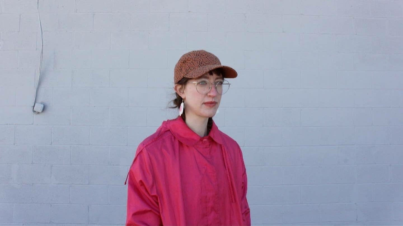 Woman in baseball cap, glasses, and pink windbreaker.