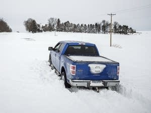 Rick Brewer, of Red Wing, Minn., sits in his pickup after getting stuck.