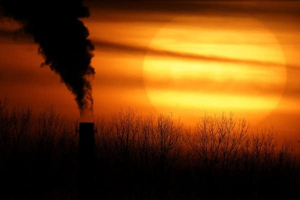Emissions from a power plant are silhouetted against the setting sun.