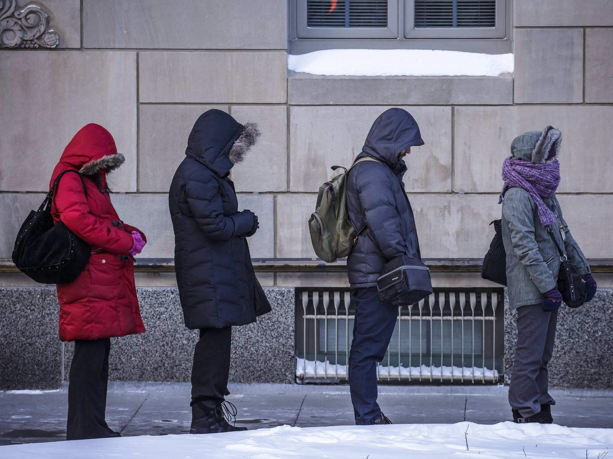 People bundled up in their hooded jackets wait for a a bus in Rochester.