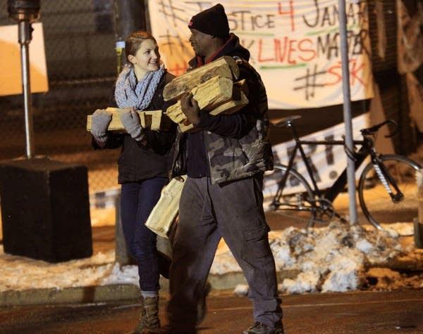 Volunteers haul donated firewood.