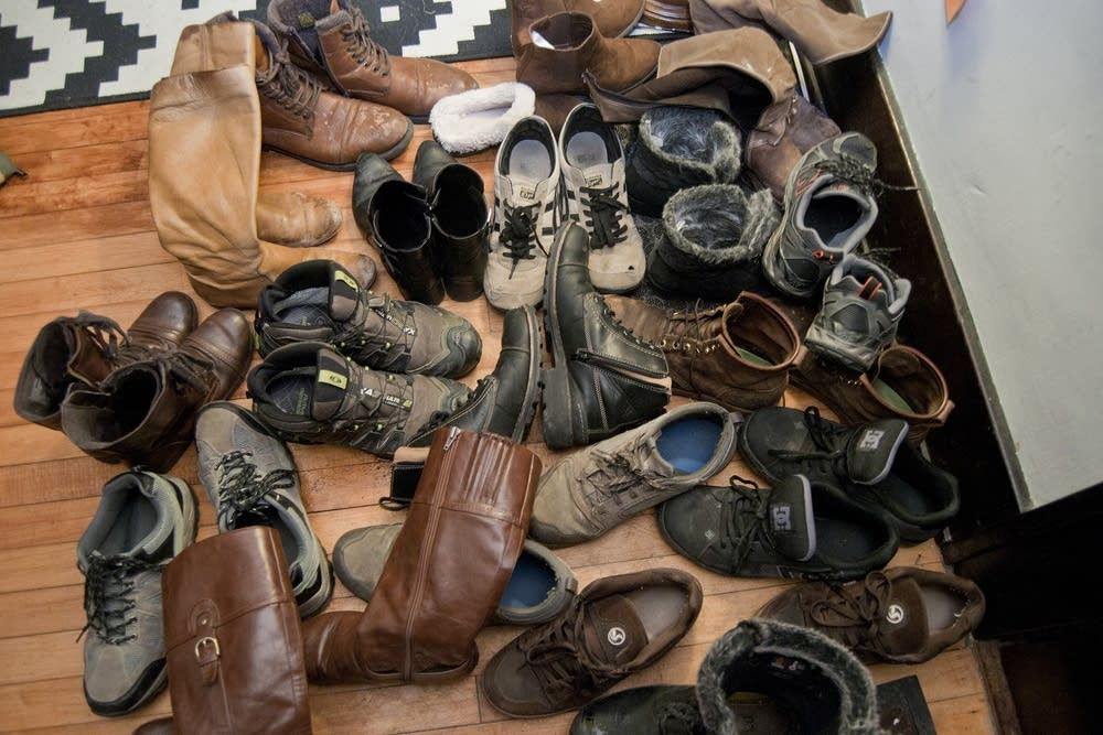 A pile of shoes in the entryway of a home concert.