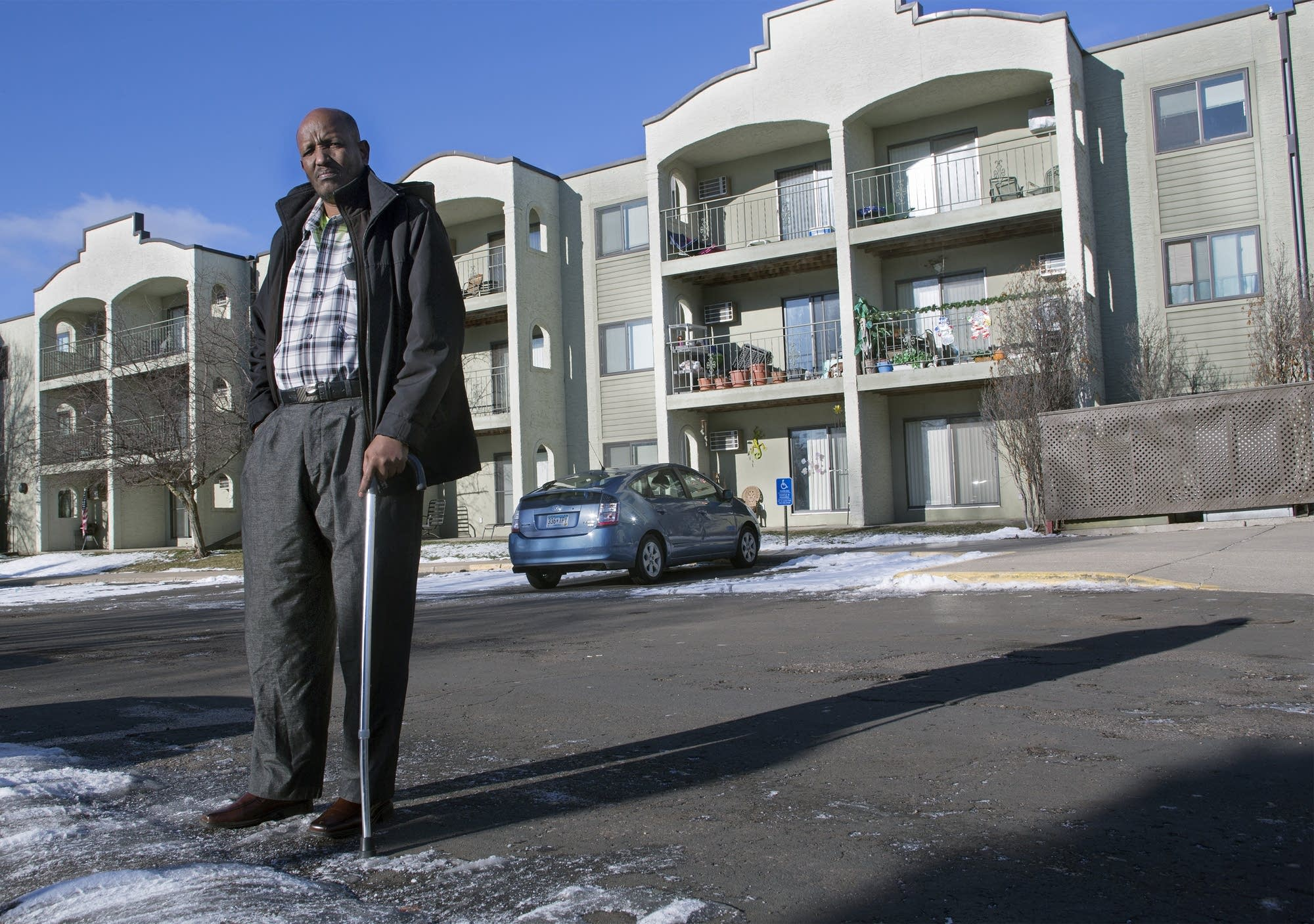 Mahamed Iye stands in front of the apartment complex where he lives.
