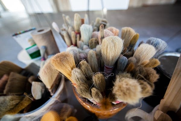 Paint brushes sit in jars