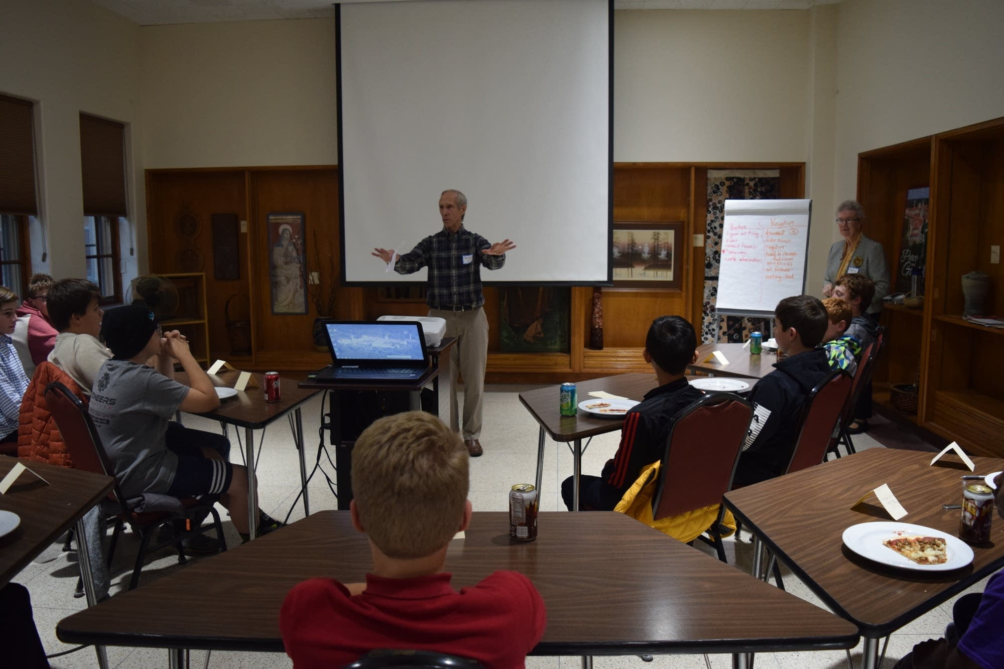 Retired teacher Jerry Hrabe talks to a group of adolescent boys.