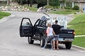Two people are seen near a black Dodge truck.