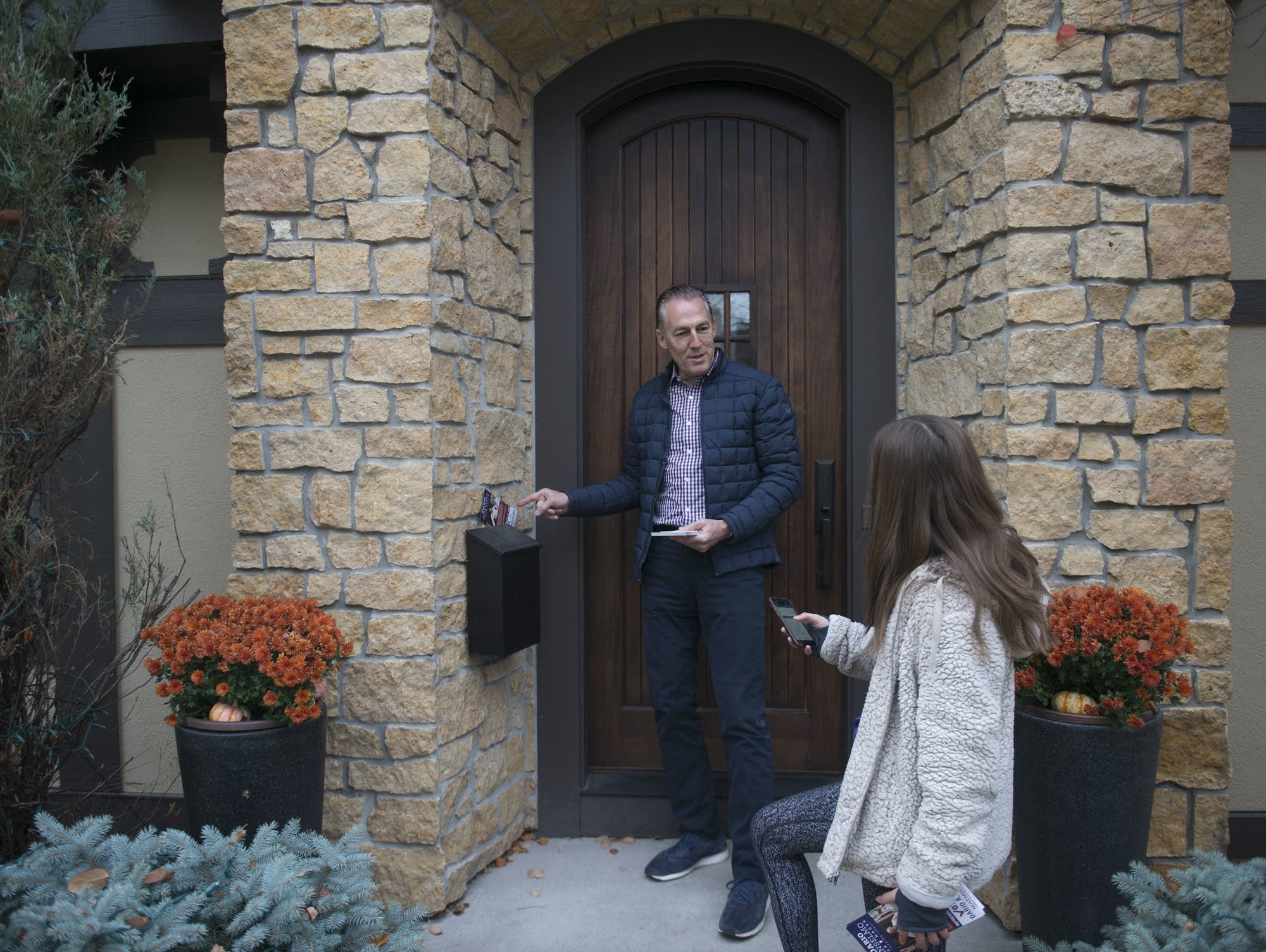 Dario Anselmo drops off voter literature at a home in Edina