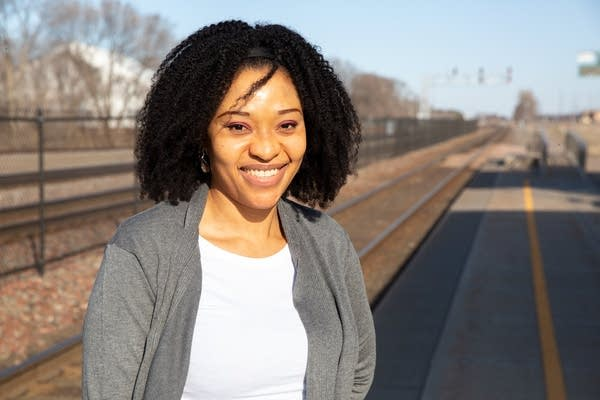 A woman stands with railroad tracks behind her.