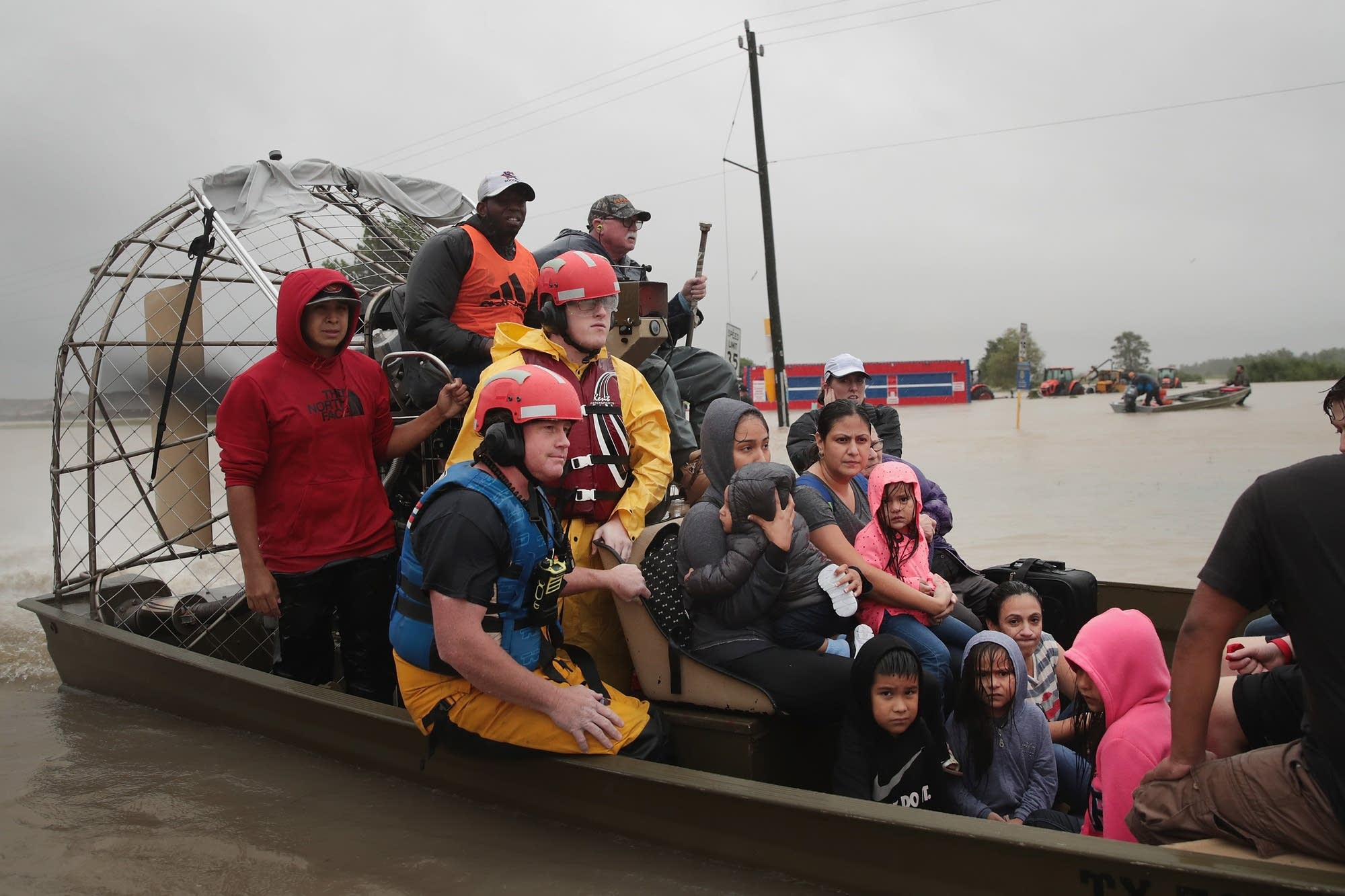 People are rescued from a flooded neighborhood.
