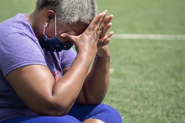 Woman wipes away tears as she cries.