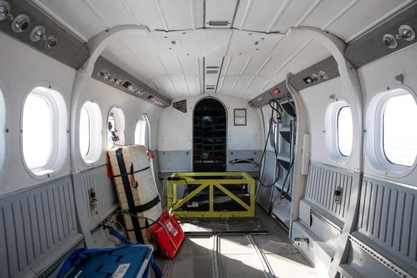 A yellow barred box holds equipment in the back of a plane.