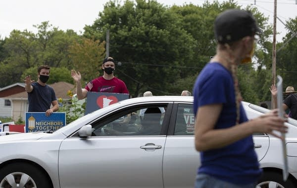 People wave to a driver.