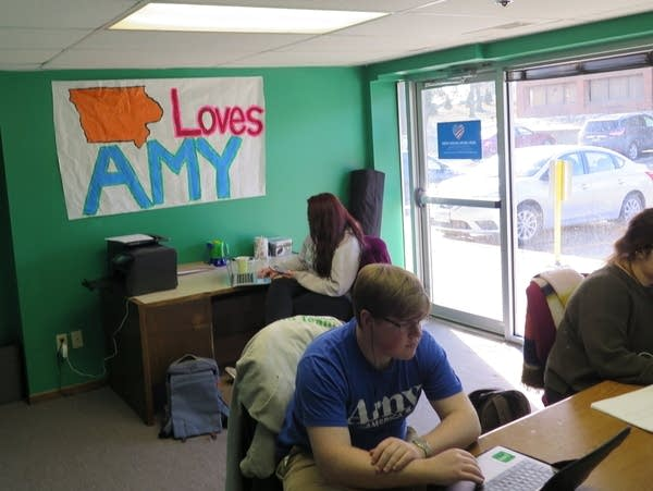 """Three people work in an office with a painted """"Iowa loves Amy"""" sign."""