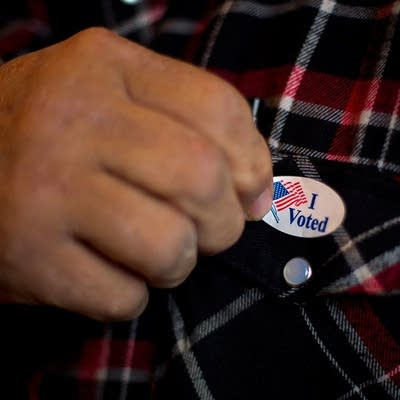 0d6a69 20151103 a man puts on his i voted sticker after voting