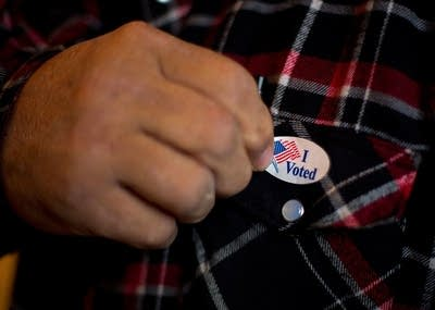 Cfa54c 20151103 a man puts on his i voted sticker after voting