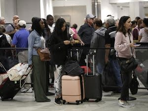 Passengers wait in line at a security checkpoint
