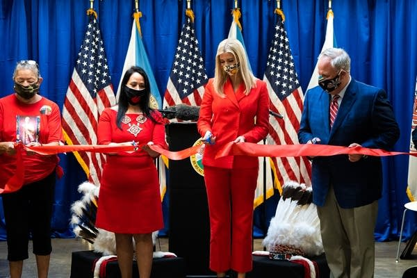 People wearing red cut a ribbon.