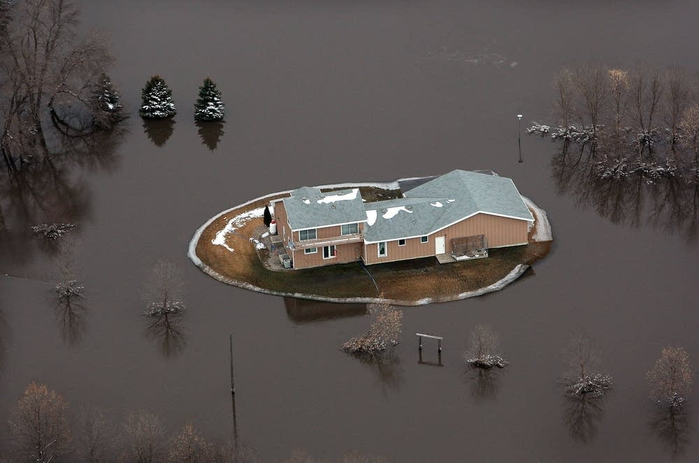 A home is surrounded by flood water from the river