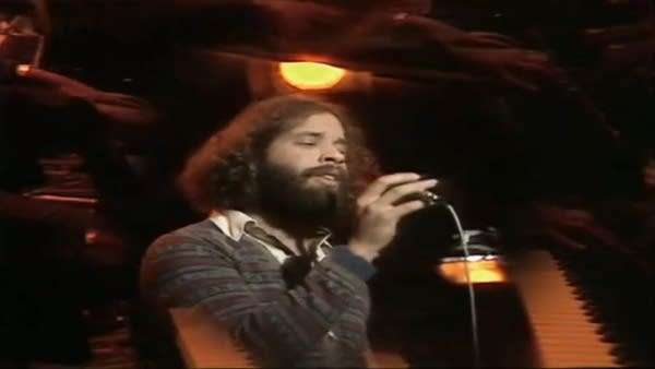 Late 1970s singer Dan Hill, white man w/ long curly hair singing into mic