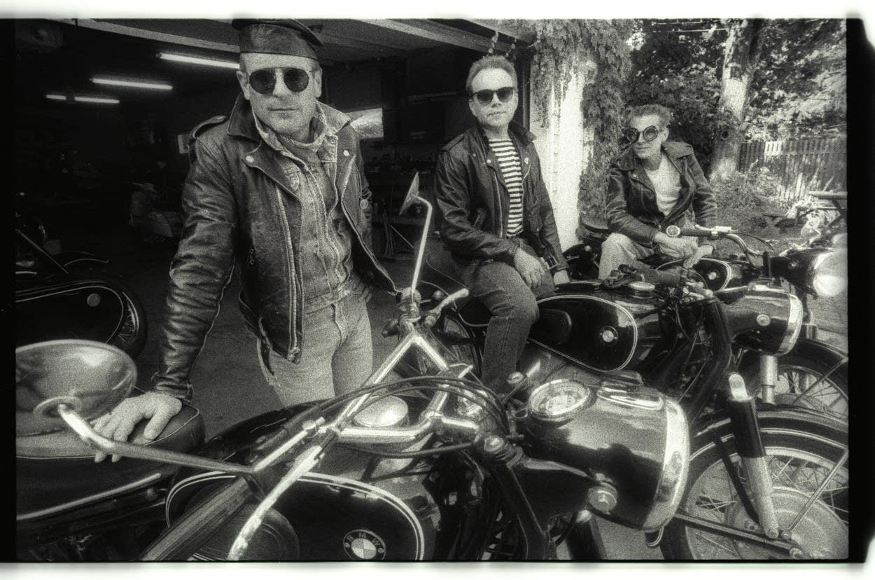 Three men with motorcycles in leather jackets.