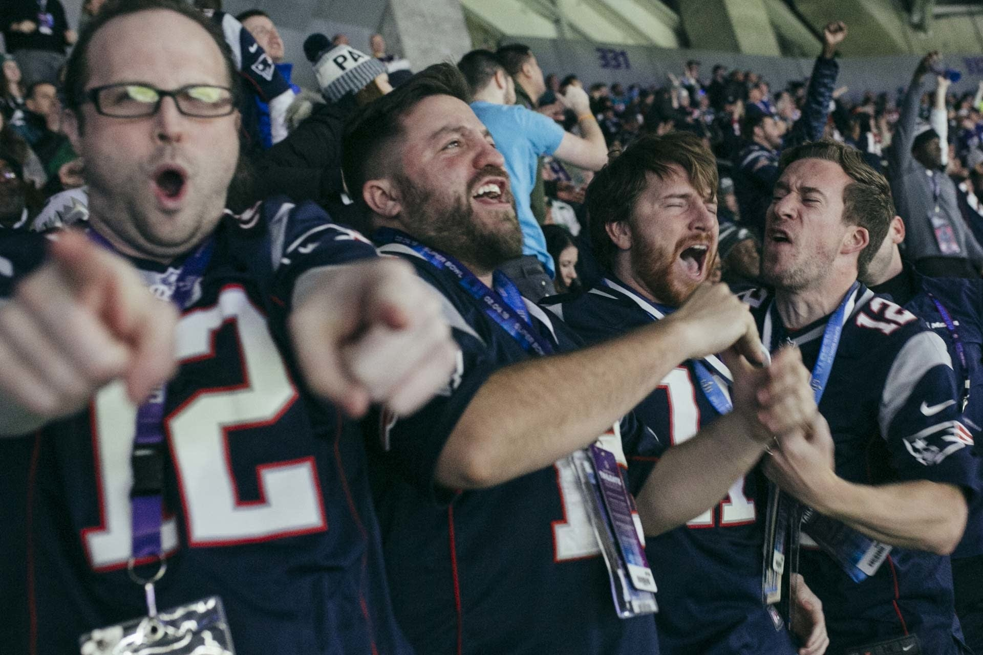 Four Patriots fan celebrate after their team scored a touchdown.