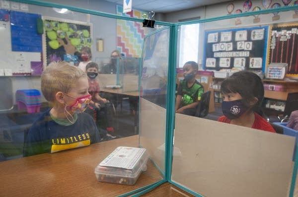 Two students look are separated by a plastic barrier.