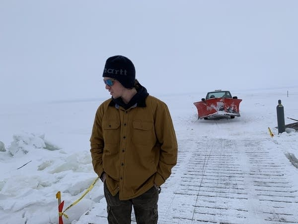 A man stands on a plank bridge with a snow plow behind him