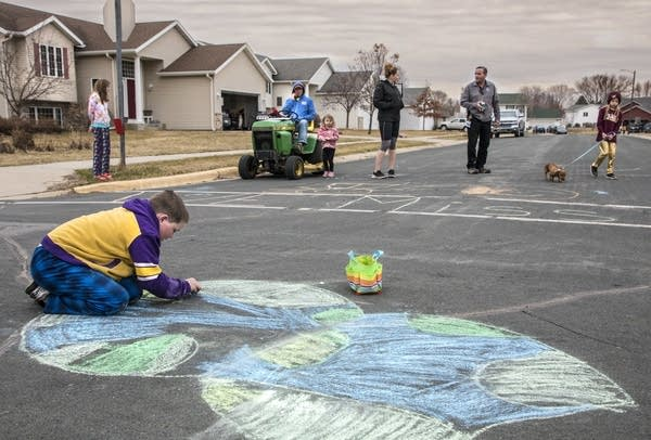 A boy draws with chalk on the street